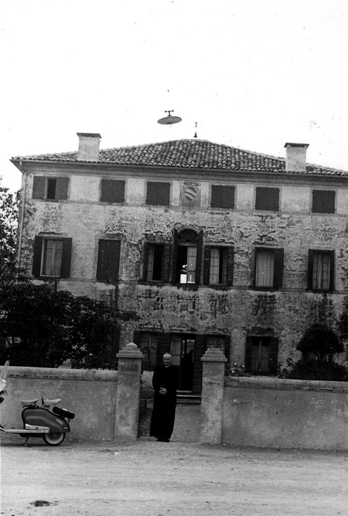 Foto Ida Trinca - La facciata a nord della canonica: sul cancelletto don Alberto Miatello